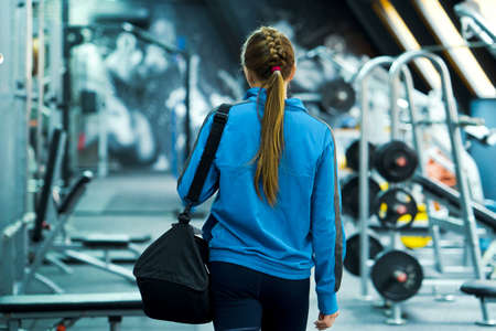 Fit woman with bag in sportswear entering gym