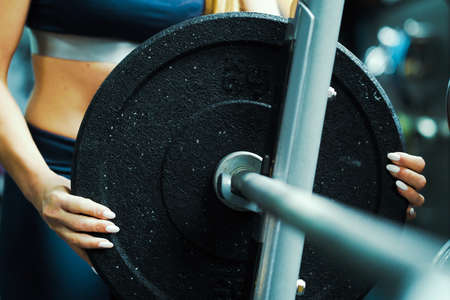 Strong woman putting weight plate on barbell in gym