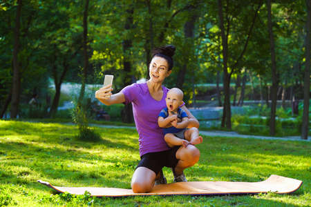 Fitness blogger with baby streaming from park 스톡 콘텐츠