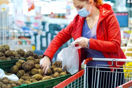 Woman picking potatoes in supermarket during pandemic 스톡 콘텐츠
