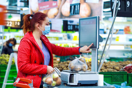 Young woman weighing vegetables at grocery store during pandemic 스톡 콘텐츠