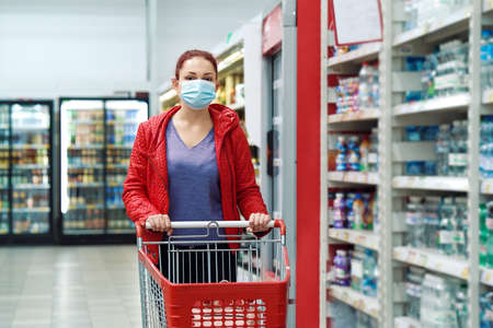 Woman wearing mask near bottled water at grocery store 스톡 콘텐츠