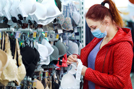 Young woman choosing bra in department store during pandemic 스톡 콘텐츠