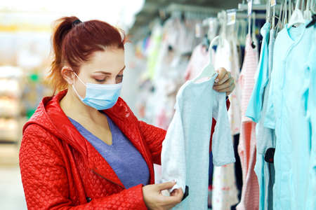 Woman in mask buying children clothes in department store during pandemic