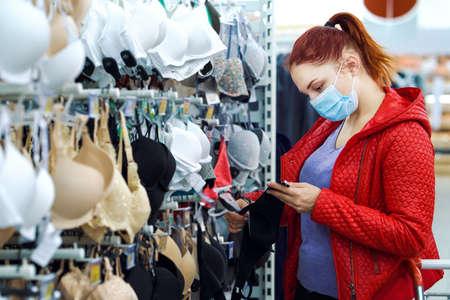 Woman in mask buying bra in supermarket