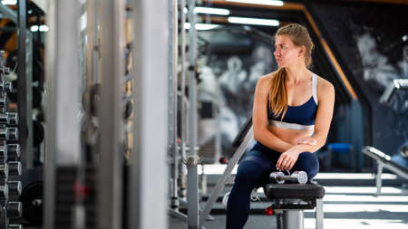 Woman relaxing after working out with dumbbells in gym