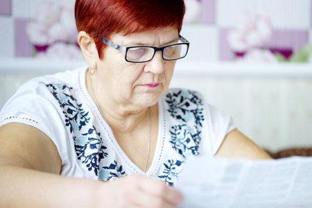 Senior woman wearing eyeglasses reading leaflet to drugs