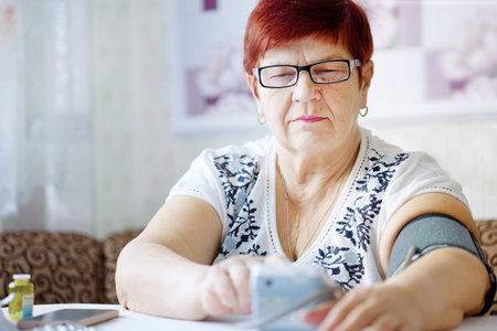 Senior woman wearing eyeglasses measuring blood pressure