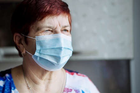 Senior woman in medical mask at home 스톡 콘텐츠