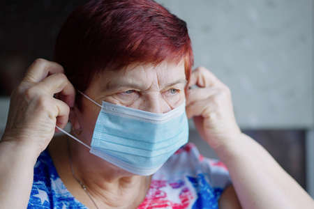 Senior woman putting on medical mask and staying at home