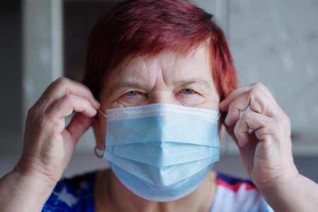 Senior woman putting on medical mask and looking at camera