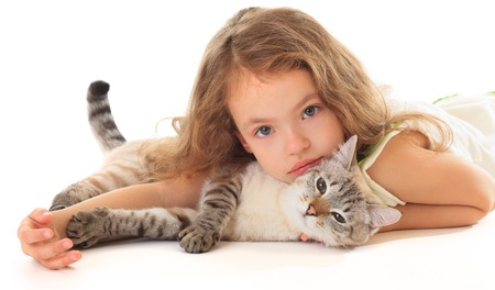 Beautiful little girl hugging her cat on a white background.