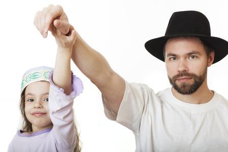 skullcap: Man in Jewish hat and girl in skullcap.
