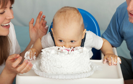 happy birthday girl: Kid eats cake. Family celebrates the first birthday of his son. Stock Photo