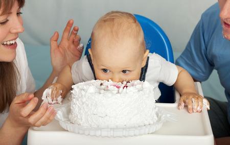 first birthday: Kid eats cake. Family celebrates the first birthday of his son. Stock Photo