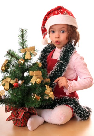 merriment: Little girl with the decorated new-year tree. Stock Photo