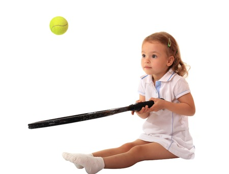 plays: A little girl plays tennis.  Isolated background.
