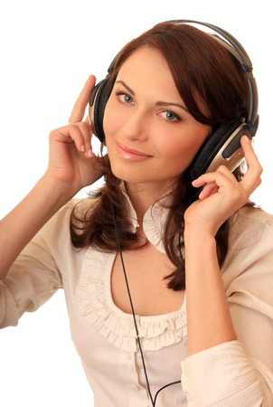 listens: A beautiful girl in headsets listens music.