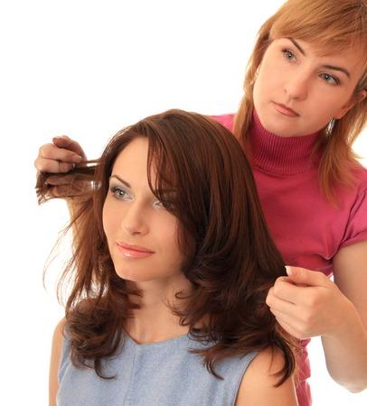 estilista: El estilista hace el pelo hermosa chica. Fondo aislado.