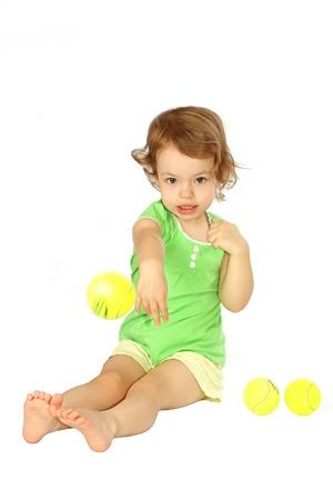 d?a: Una ni�a da una pelota de tenis.