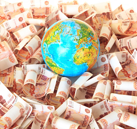 dearly: Globe against five thousandth Russian banknotes. Isolated background.