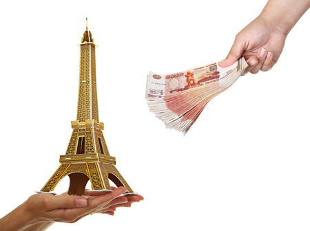thousandth: Model Eiffel Tower and a pack of five thousandth of notes in womens hands. Stock Photo