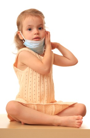 pity: A little girl puts on a non-permanent medical mask. Stock Photo