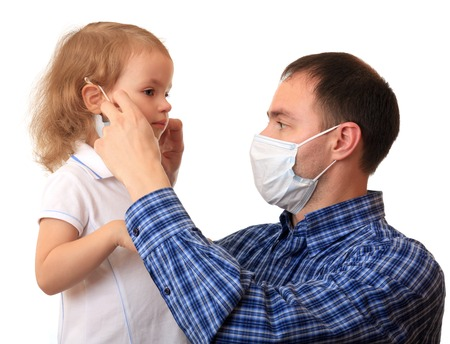 A dad puts a non-permanent medical mask on to daughter.
