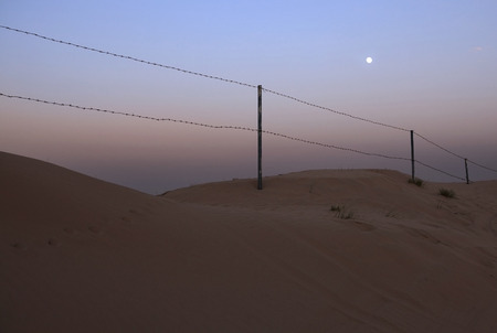 barbed wire fence: Fence of barbed wire in the desert. Moonlit night. Stock Photo