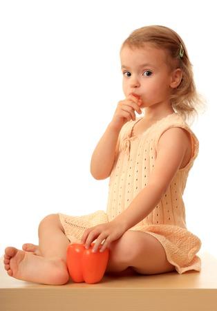 eats: A little girl eats a sweet pepper.