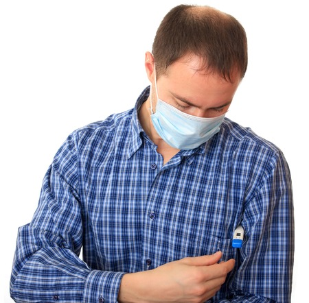 prophylactic: Man in a non-permanent medical mask with a thermometer.