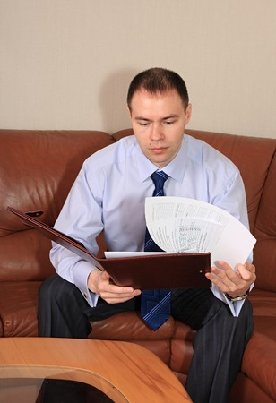 presentiment: A businessman studies an agreement in office.