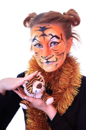 Tiger cub: Muchacha en aspecto un tigre con un cachorro de tigre del juguete. En un calendario de este nuevo a�o 2010 - a�o del tigre.