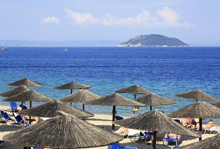 sithonia: Sithonia, Greece - July 20, 2014: Parasols of straw on the beach and Kelyfos (Turtle) Island Editorial