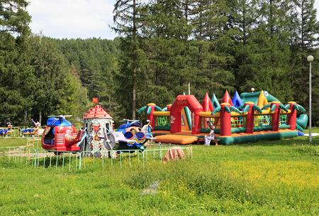belokurikha: Belokurikha, Russia - August 07, 2013: Childrens carousel and inflatable trampoline in resort Belokurikha. Editorial