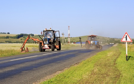 mows: Tractor mows the grass on the side of the road. Altai Krai in Russia. Stock Photo