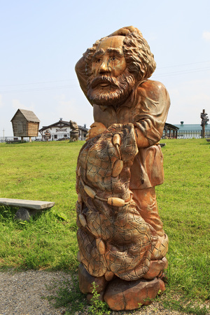 woodland sculpture: Novotyryshkino, Russia - July 31, 2013: Old man with a seine. Wooden sculptures based on Pushkins fairy tales. Tourist Complex Siberian Podvorye. Editorial
