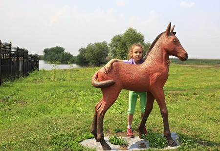 woodland sculpture: Novotyryshkino, Russia - July 31, 2013: Little girl and sculpture foal. Tourist Complex Siberian Podvorye.