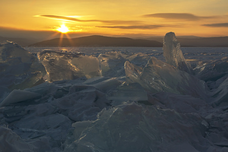 Transparent pieces of ice and rising sun. Beautiful winter landscape in the Lake Baikal. Standard-Bild