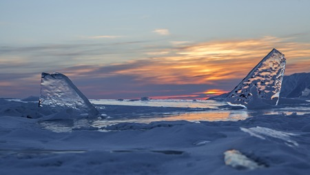 Transparent icicles at sunset. Beautiful winter landscape in the Lake Baikal.