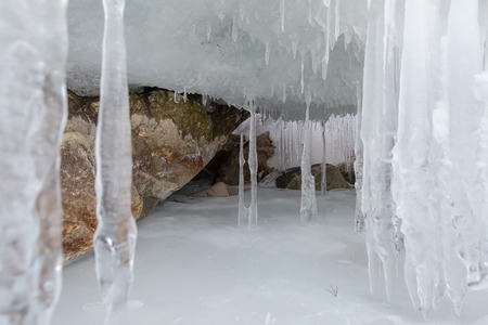 hummock: Huge icicles on a cliff. Beautiful winter landscape in the Lake Baikal. Stock Photo