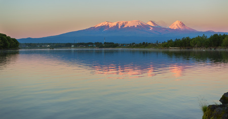 Sunset lighting Kluchevskaya group of volcanoes with reflection in the river Kamchatka.