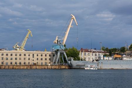 Sevastopol, Russia - June 09, 2016: Lifting cargo cranes at the shipyard in Bay of Black Sea. Editorial