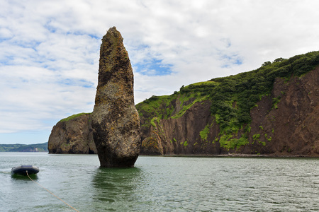 Sea stack Womans happiness in the Avacha Bay of the Pacific Ocean. The coast of Kamchatka.