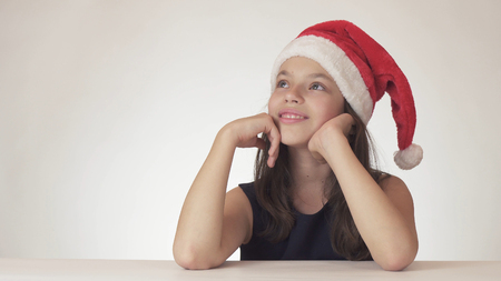 Beautiful teen girl in Santa Claus hat sitting and dreaming of a gift, expresses happiness and anticipation on a white background