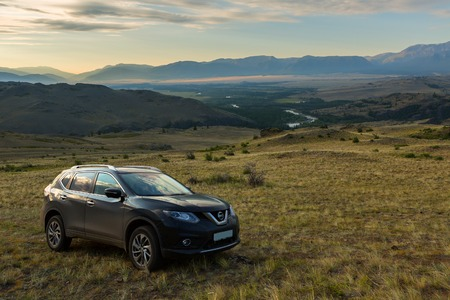 Altai Krai, Russia - July 15, 2015: Crossover Nissan X-TRAIL on the hillside in the Kurai steppe against the backdrop of the North Chuy ridge at dawn. 에디토리얼