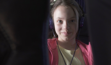 Cheerful teenage girl listens to music on headphones in the cabin of a plane while traveling