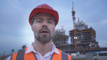 Man in a helmet, architect, engineer, manager tells about the progress of construction in the evening