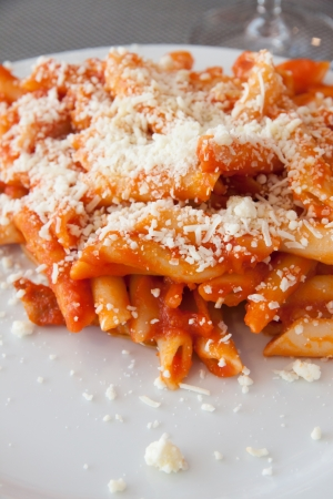 A tipicall italian dish of pasta  penne with tomato sauce and parmisan cheese photo