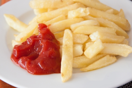 A dish of chips with a lot of ketchup photo